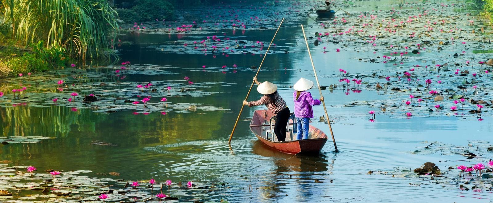 Locaux pagayant en pagode à travers les eaux de Hanoï au Vietnam.